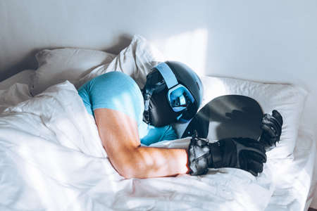 man in bed with snowboard ski googles and helmet dreaming about snow mountains