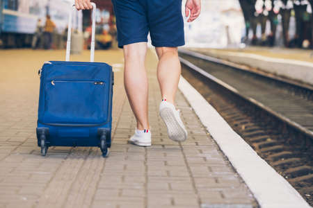 man with suitcase on wheels walking by railway station platform travel concept