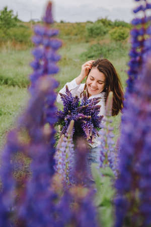 woman at blooming lupines field Banque d'images - 151505252