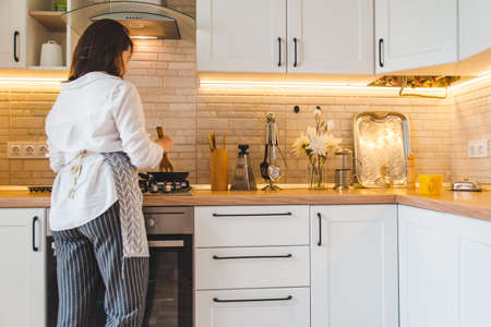 view from behind woman on kitchen cooking