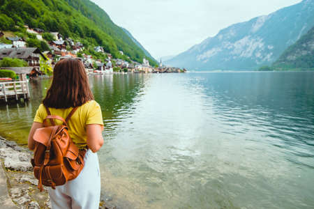 woman standing on the beach looking at hallstatt city in austrian alpine Banque d'images