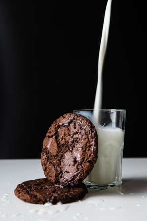 pouring milk in glass with chocolate cookies Banque d'images