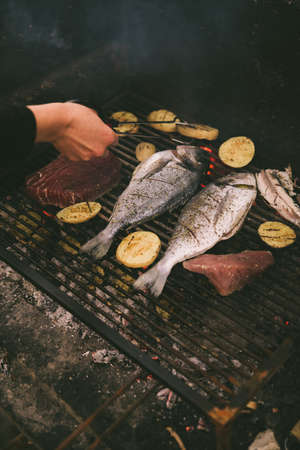 cooking fish and potatoes on grill