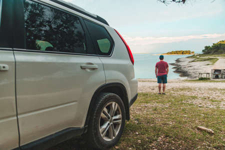 tourist man standing at sea beach suv car on front