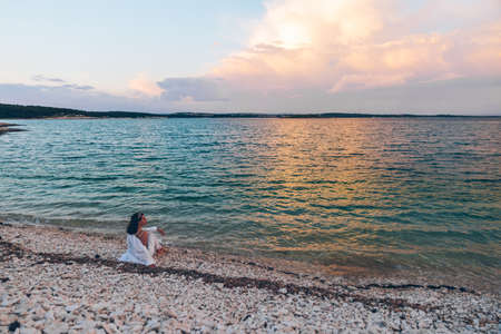 young pretty woman sitting on the beach looking on sunset above the sea