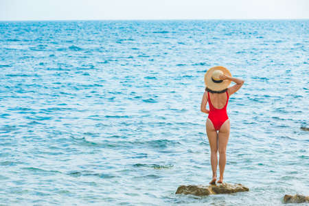 young pretty woman in straw hat at sea beach summer vacation red swimsuit