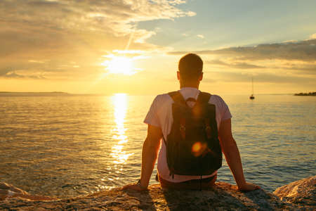 man with backpack enjoying sunset over the sea. copy space. summer vacation