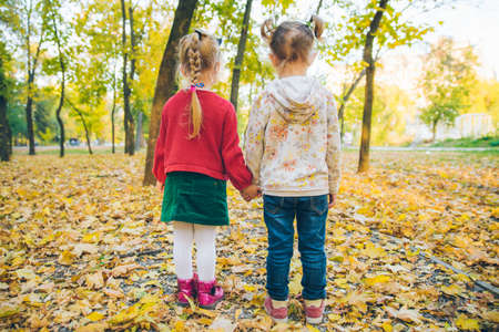 two little girls girlfriends playing at autumn city park holding hands activities