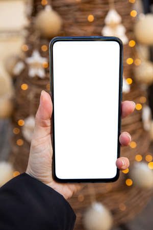 woman hand holding phone with white screen christmas tree on background copy space