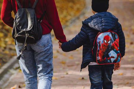 Lviv, Ukraine - October 24, 2019: mother with kid walking by autumn public park. copy space