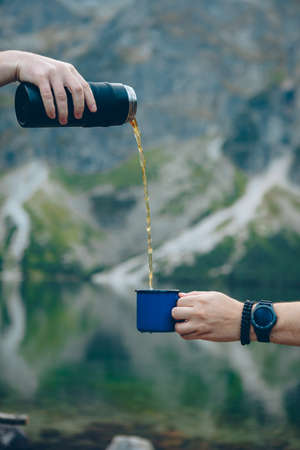 pouring tea from  to cup hiking concept lake  mountains on background warm up drink