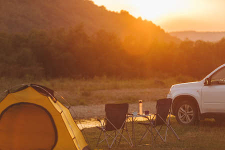 camping at beach of mountain river. suv car. yellow tent. camp table and chairs. copy space