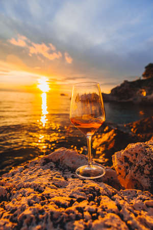 glass of wine at rocky sea beach on sunset. copy space. summer vacation