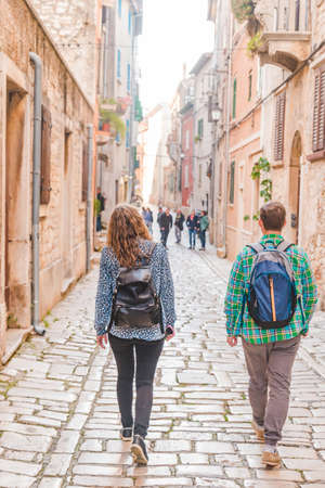couple tourists with backpack walking by old streets of Rovinj city. Croatia. Summer time