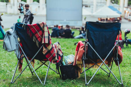 two folding chairs with cooling bag with beer and snacks in open air cinema copy space Reklamní fotografie