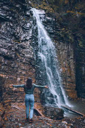 woman in casual clothes looking at waterfall copy space Reklamní fotografie