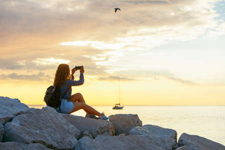 woman with backpack looking on sunset over the sea. copy space