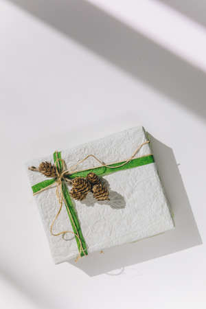present gift box wrapped with white paper and green ribbon top view