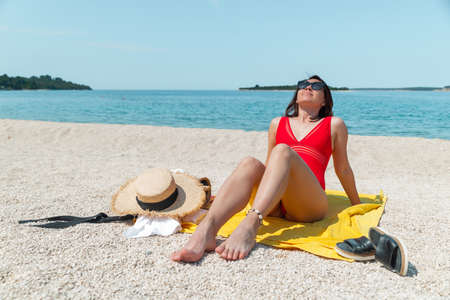 women in red swimsuit laying at sunny sea beach
