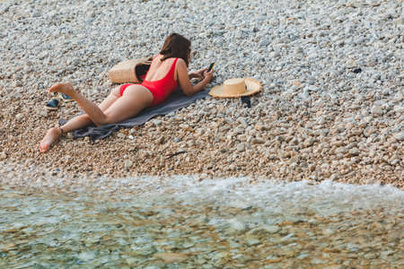 young pretty woman laying at rocky beach suntanning summer time copy space