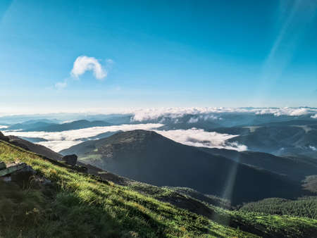 summer view from mountain peak to blue sky with clouds below
