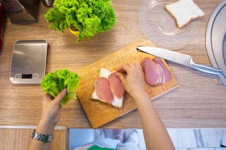 making sandwich slicing ham on cutting board copy space Standard-Bild