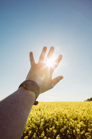 man hands with watch on wrist sun rays goes though fingers copy space Standard-Bild
