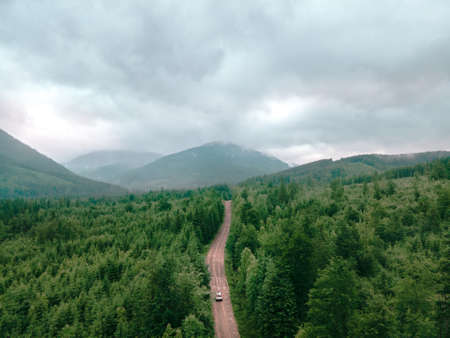 aerial view of carpathian mountains overcast weather suv car on trail road copy space Standard-Bild