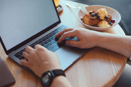 freelancer working remotely at the cafe plate with dessert copy space