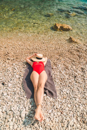 woman laying on blanket at sea beach copy space Standard-Bild