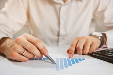 Business person analyzing financial statistics displayed on the tablet