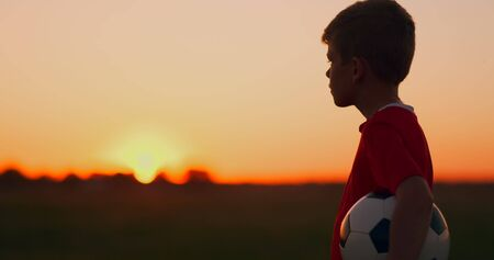 Young football player goes with the ball on the field dreaming of a football career, at sunset looking at the sun