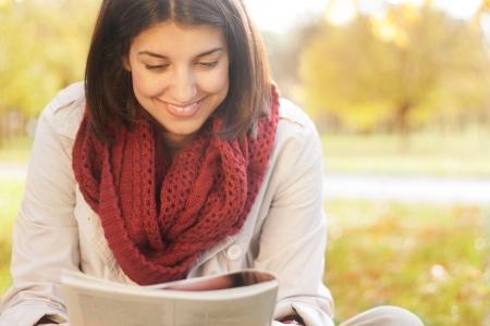 mujer leyendo libro: Mujer joven en parque del autmn