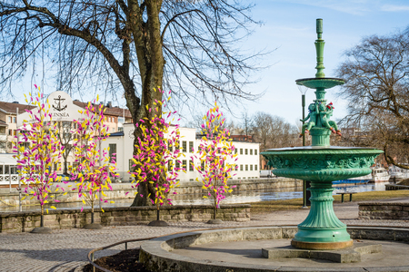 UPPSALA, SWEDEN - Mar 26, 2016 - Street view of inactive fountain with traditional colourful feathers on trees for Easter decorations in Uppsala, Sweden, Europe Editorial