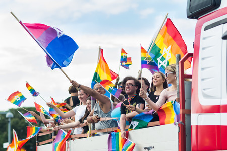 STOCKHOLM, SWEDEN – JULY 30, 2016: People in the truck waving rainbow flags with Jewish star during Stockholm Pride Parade on Hantverkargatan near the City Hall Editorial