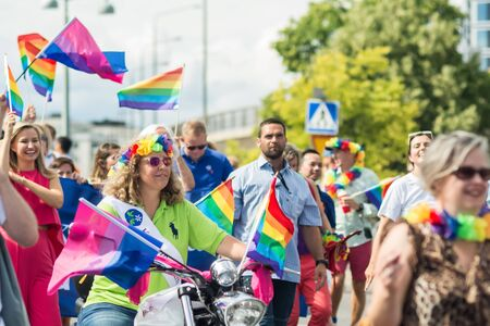 bandera de suecia: STOCKHOLM, SWEDEN – JULY 30, 2016: Woman riding motorbike with rainbow flags in the crowd during Stockholm Pride Parade on Hantverkargatan near the City Hall Editorial