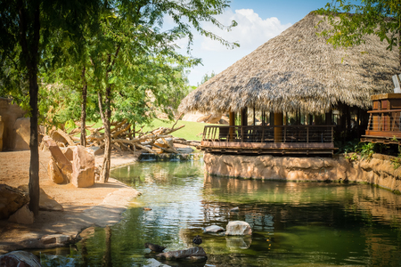 Perfect place for chilling at a restaurant looking like a rustic wooden house with straw roof, in a zoo, near water, surrounded by green trees, on hot summer day
