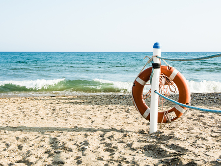 Lifebuoy on a sandy sea beach in Terracina, Italy. Safe swimming in the sea and ocean. Background for a marine theme or safety during vacation