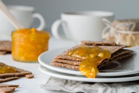 Closeup of brown rye crisp bread (Swedish crackers) with spread orange jam, on white background. Sweet snack or breakfast Stock Photo