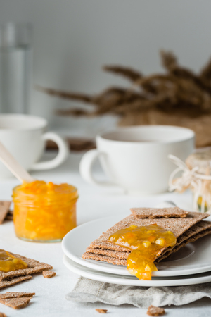 Brown rye crisp bread (Swedish crackers) with spread orange jam and cups of tea, on white background. Sweet snack or breakfast