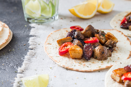 Tacos with grilled mushrooms, Spanish spicy sausage chorizo, Mexican tortillas, Cypriot cheese halloumi, hot chilly, dried oregano. With glass of water with lime and lemon on cloth background Stock Photo