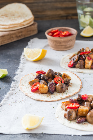 Tacos with grilled mushrooms, Spanish spicy sausage chorizo, Mexican tortillas, Cypriot cheese halloumi, hot chilly, dried oregano, slices of lime and lemon, glass of water, on cloth Stock Photo