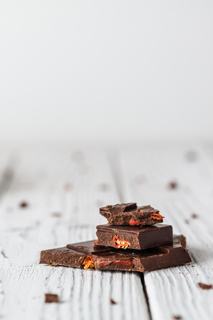 Raw handmade chocolate with goji on white wooden background. Healthy sweets concept. Copy space