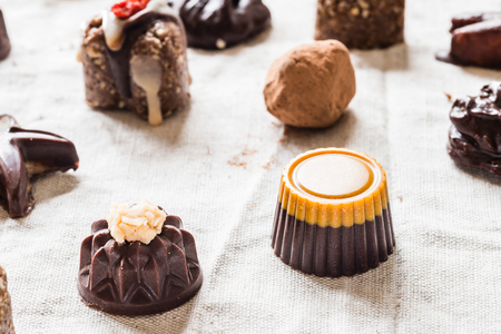 Variety of raw chocolate candies, homemade vegan sweets of different shapes on cloth background