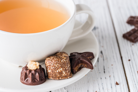 Cup of tea with raw handmade chocolate candies on white wooden background. Healthy breakfast with vegan sweets