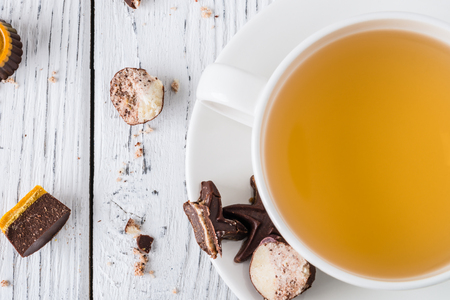 Cup of tea with raw handmade chocolate candies on white wooden background. Healthy breakfast with vegan sweets. Top view
