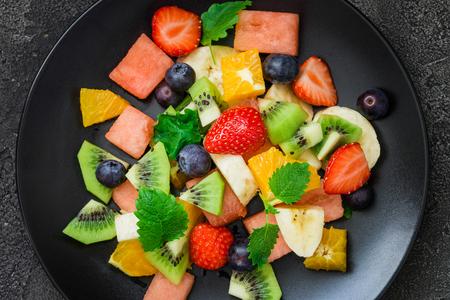 lemon balm: Healthy fresh fruit salad on black plate on dark background. Top view. Delicious summer meal: strawberries, blueberries, oranges, kiwi, banana, watermelon, balm mint