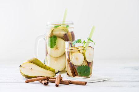 lemon balm: Refreshing drink with pear, cinnamon sticks on white rustic table. Easy to do and tasty summer drink concept