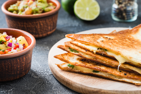 Grilled quesadillas (tortillas with cheese) on wooden board and two spicy dips: pineapple salsa and guacamole. Dark background. Mexican cuisine concept