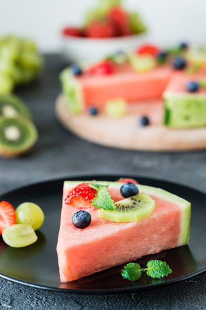lemon balm: Slice of watermelon pizza with fruits: strawberry, kiwi, grapes, blueberry and mint, on black plate. Dark background. Selective focus Stock Photo
